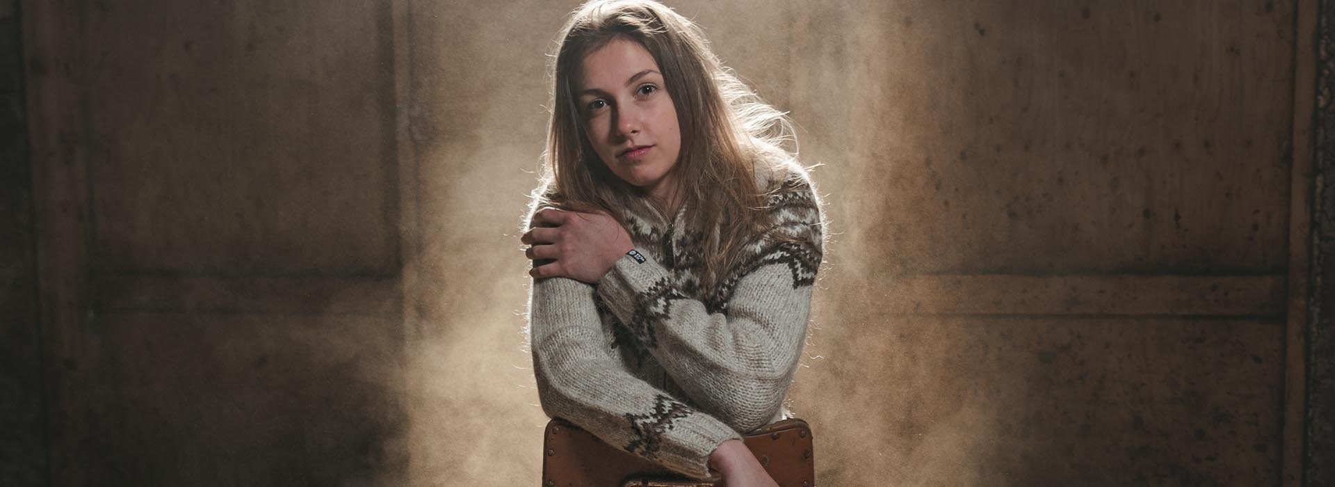 young woman sitting dressed in wool sweater